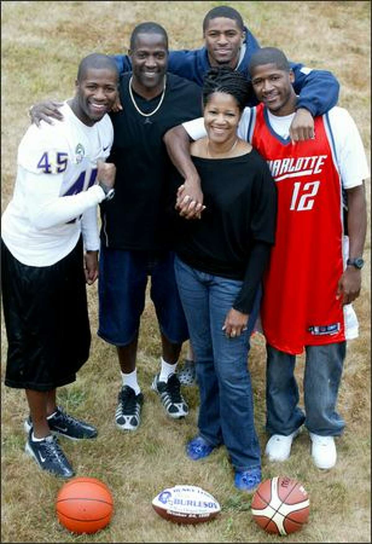 Valerie Burleson and husband Al, second from left, huddle with three of their athletic sons in the backyard of their Renton home. Their four sons include Al Jr., left, Lyndale, rear, Kevin, right, and Nate, not pictured.
