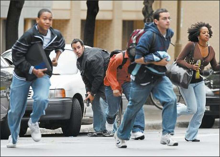 As a plainclothes police officer looks on, students run for cover after a gunman opened fire Wednesday at Dawson College in Montreal. Photo: / Associated Press