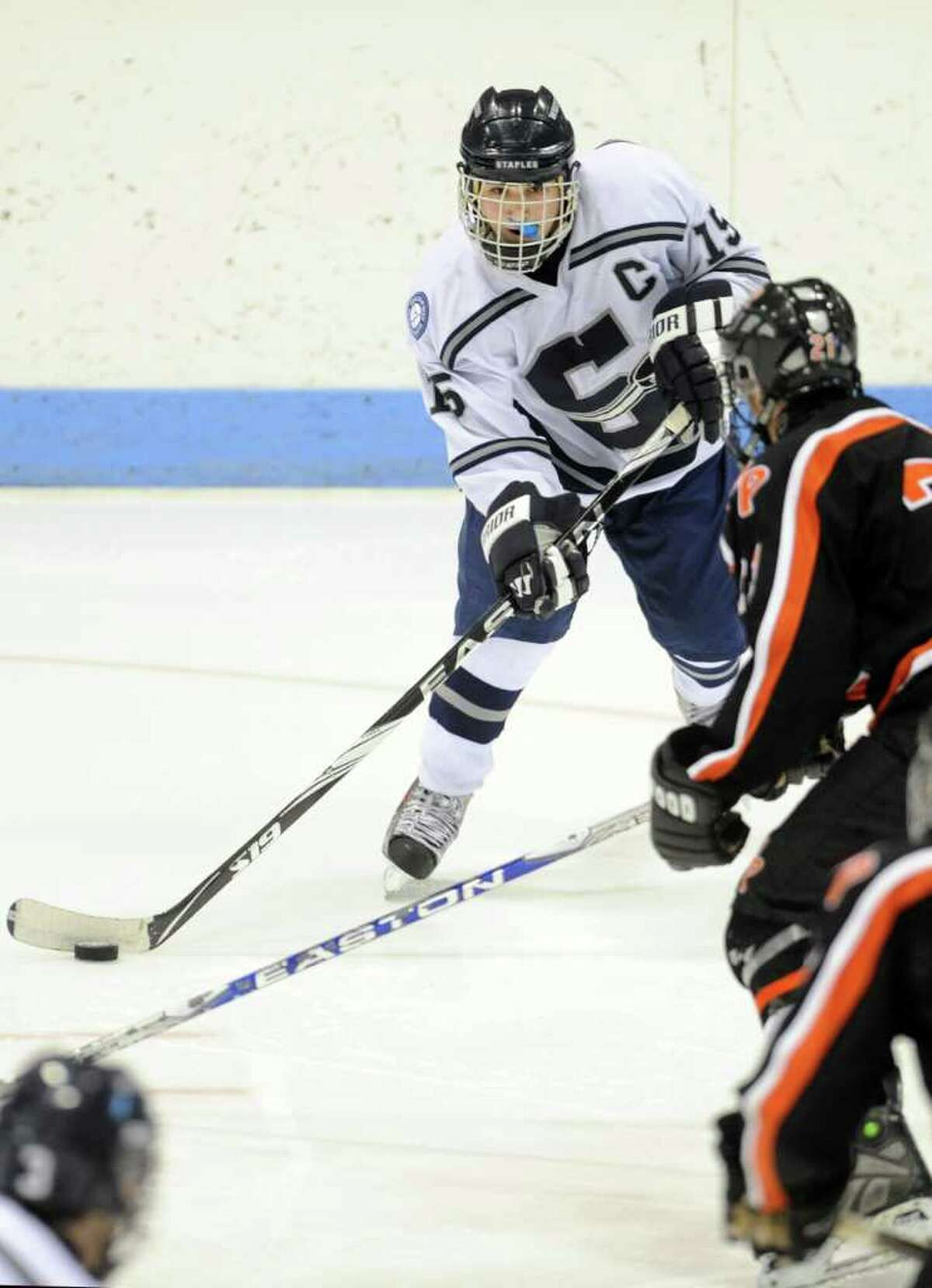 Staples' Kyle Wehmhoff controls the puck as Watertown-Pomperaug's Brian Fay moves in to defend during the Division III state playoff game at Yale University's Ingalls Rink Saturday, Mar. 19, 2011.