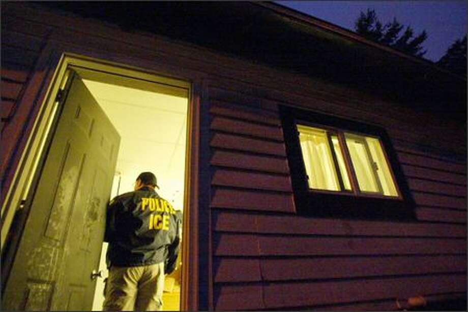 Immigration and Customs Enforcement agents arrest two illegal immigrants during a pre-dawn raid on their Everett home. The men likely will be deported. Photo: Paul Joseph Brown/Seattle Post-Intelligencer