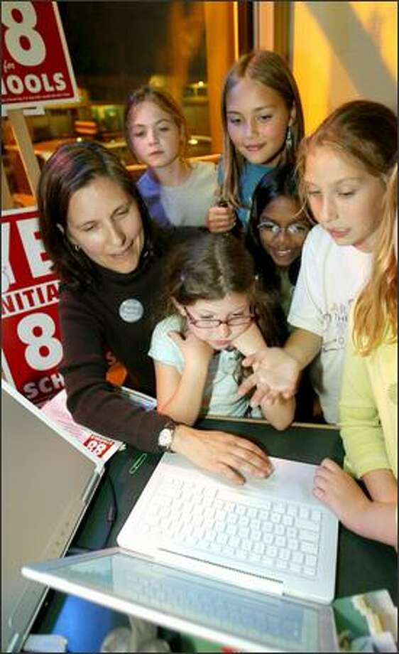 I-88 fan Beth Sanders, left, and Montlake students, clockwise bottom, Sophie Kaplan, Josie Wilson, Audrey Josephson-Day, Parkavi Turner and Claire Baker, check election results Tuesday. Photo: Scott Eklund/Seattle Post-Intelligencer
