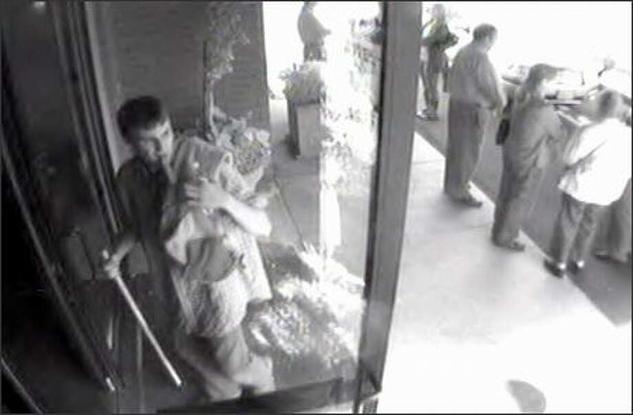 Seattle police are asking for help identifying this man seen on surveillance video at Evergreen-Washelli cemetery. A man with a knife stole a woman's car as she visited her father's grave. Photo: /