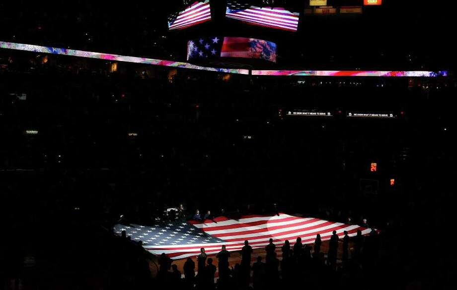 FOR SPORTS - An American flag is displayed on the court during the national anthem before the  Spurs and  Bobcats game Saturday March 19, 2011 at the AT&T Center for military appreciation night.  (PHOTO BY EDWARD A. ORNELAS/eaornelas@express-news.net) Photo: EDWARD A. ORNELAS, SAN ANTONIO EXPRESS-NEWS / SAN ANTONIO EXPRESS-NEWS NFS