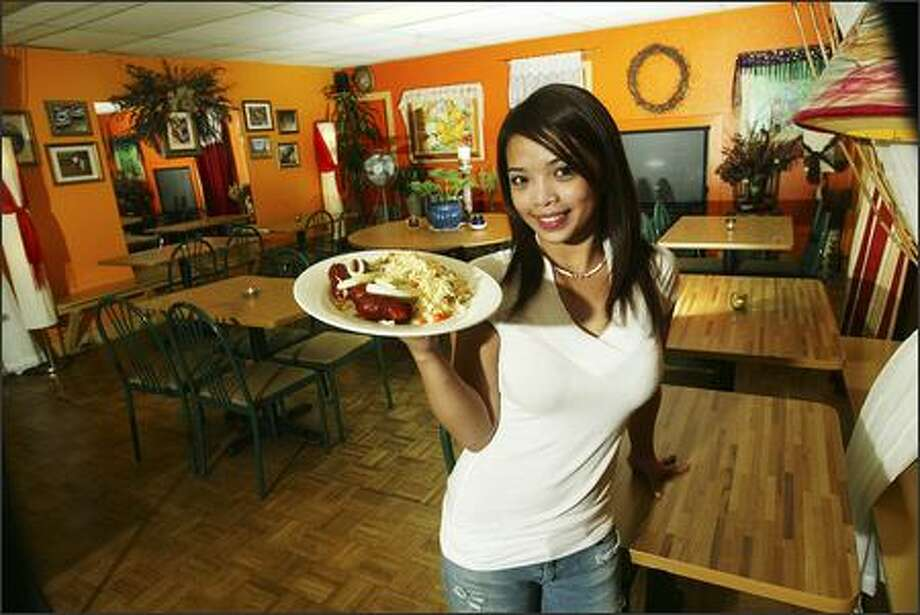 Kusina Filipina server Paula Paraiso displays a plate of Longanisa sausage and rice ($5.49). Most dishes at the big, cheery eatery with orange walls and magenta curtains are distinct and traditional. Photo: Grant M. Haller/Seattle Post-Intelligencer