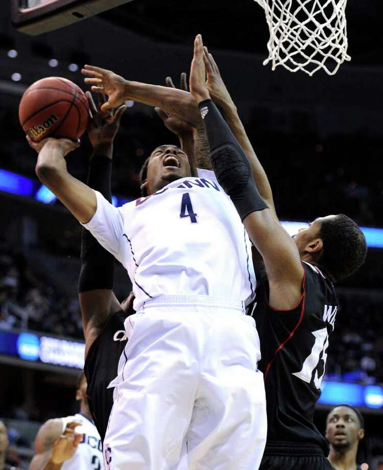 Connecticut forward Jamal Coombs-McDaniel (4) tries to shoot past Cincinnati forward Darnell Wilks, right, during the first half of the West Regional third-round NCAA tournament college basketball game, Saturday, March 19, 2011, at the Verizon Center in Washington.  (AP Photo/Nick Wass) Photo: AP