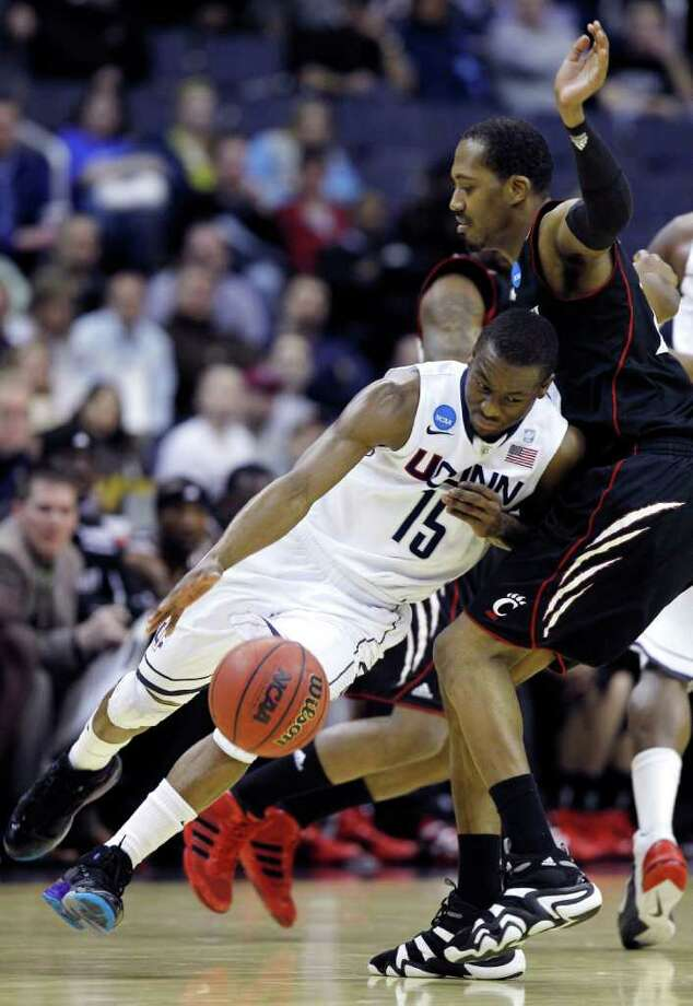 Connecticut guard Kemba Walker (15) drives into Cincinnati forward Darnell Wilks during the first half of the West Regional third-round NCAA tournament college basketball game, Saturday, March 19, 2011, at the Verizon Center in Washington.  (AP Photo/Alex Brandon) Photo: AP