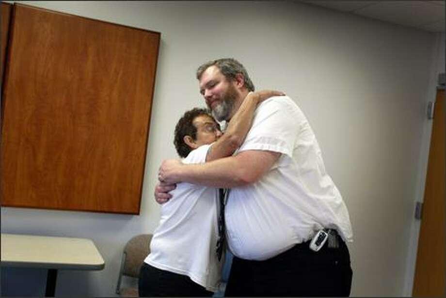 Chaplain Allan Grazier hugs Gemini Coxon, whose husband is in the intensive care unit at Harborview Medical Center in Seattle. Photo: Joshua Trujillo/Seattle Post-Intelligencer