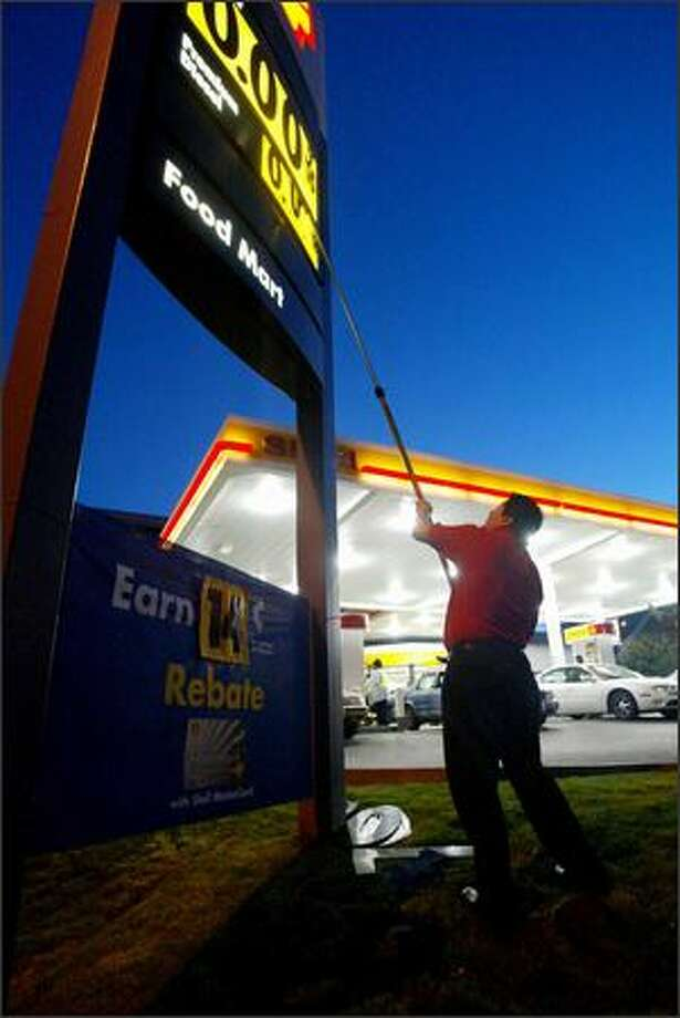 Carlos Rodriguez changes the gas-price sign at the Shell station on Lower Queen Anne to promote a free-gas giveaway.  Drivers who dropped in between 6:30 a.m. and 9:30 a.m. and between 4 to 7 p.m. receive $25 worth of free fuel as a promotion for AOL's Gold Rush. Photo: Paul Joseph Brown/Seattle Post-Intelligencer