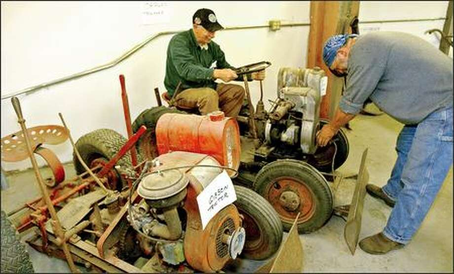 Jerry Senner, left, and Steve Rizzo, a volunteer, work on a pair of orphan tractors from the 1940s for display in the Western Heritage Center Interactive Museum at the Evergreen State Fairgrounds in Monroe. Photo: Grant M. Haller/Seattle Post-Intelligencer