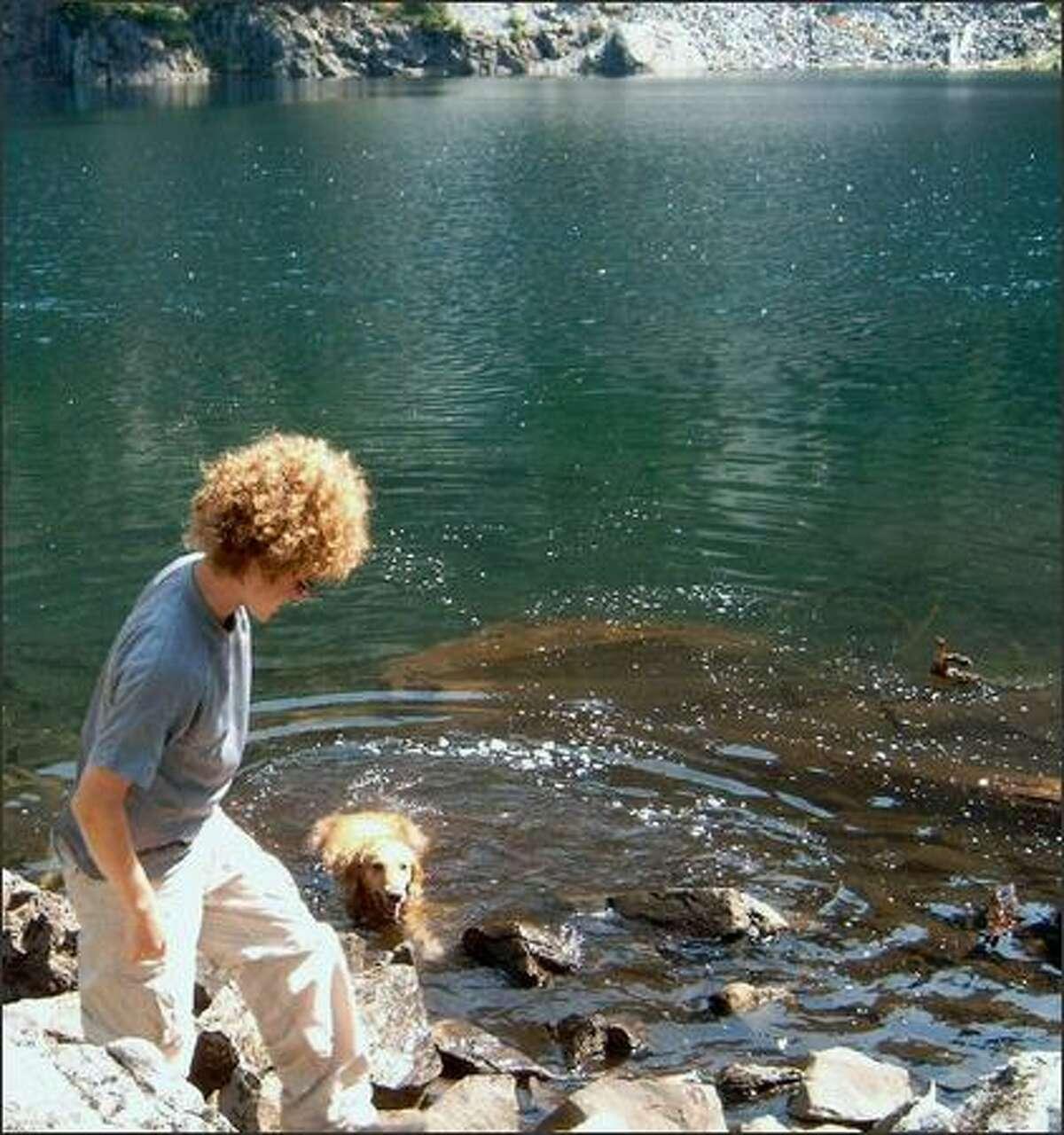 Brent Williams of Issaquah takes a break at Melakwa Lake as his golden retriever, Tika, goes for a refreshing dip.