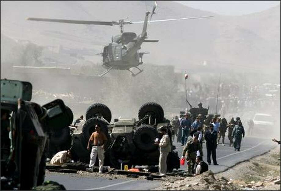 A helicopter carries the body of an Italian soldier killed after a bomb attack against a NATO patrol south of Kabul, Afghanistan, on Tuesday. The attack also killed a child behind the convoy. Photo: / Associated Press