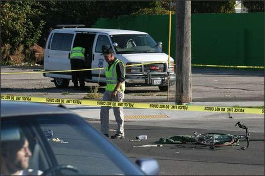 Investigators examine the accident scene at 35th Avenue Southwest and Southwest Graham Street. Photo: Meryl Schenker/Seattle Post-Intelligencer