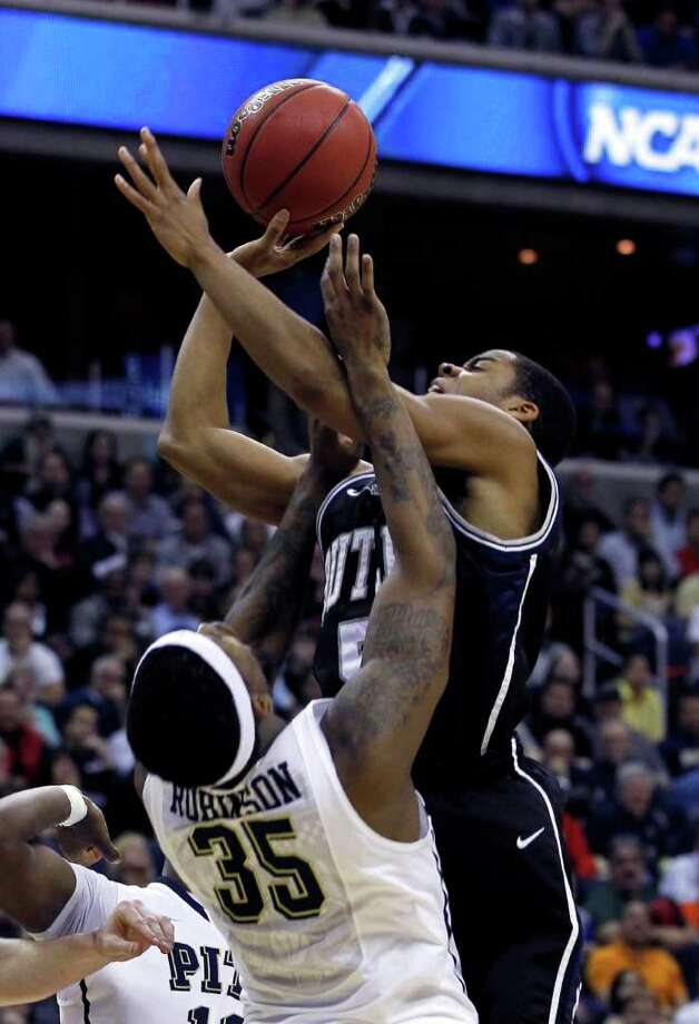 Butler guard Ronald Nored, right, shoots over Pittsburgh forward Nasir Robinson (35) during the second half of the Southeast Regional third-round NCAA tournament college basketball game, Saturday, March 19, 2011, at the Verizon Center in Washington.  (AP Photo/Alex Brandon) Photo: Alex Brandon