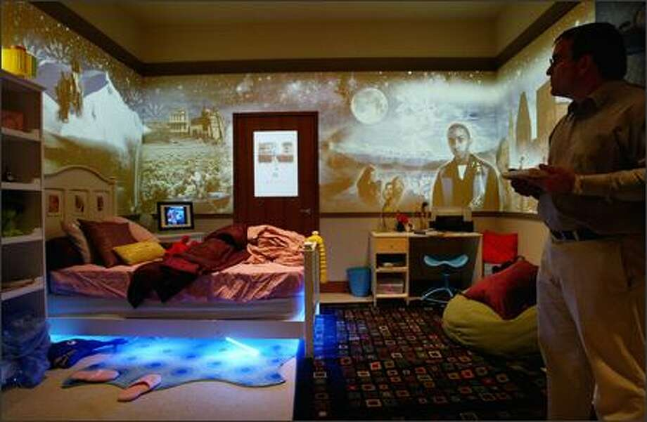 Jonathan Cluts, Microsoft's director of consumer prototyping and strategy, uses a ultramobile PC on Wednesday to create and control a collage of digital images projected on the walls of a child's bedroom in the Microsoft Home on the Redmond campus. Photo: Dan DeLong/Seattle Post-Intelligencer