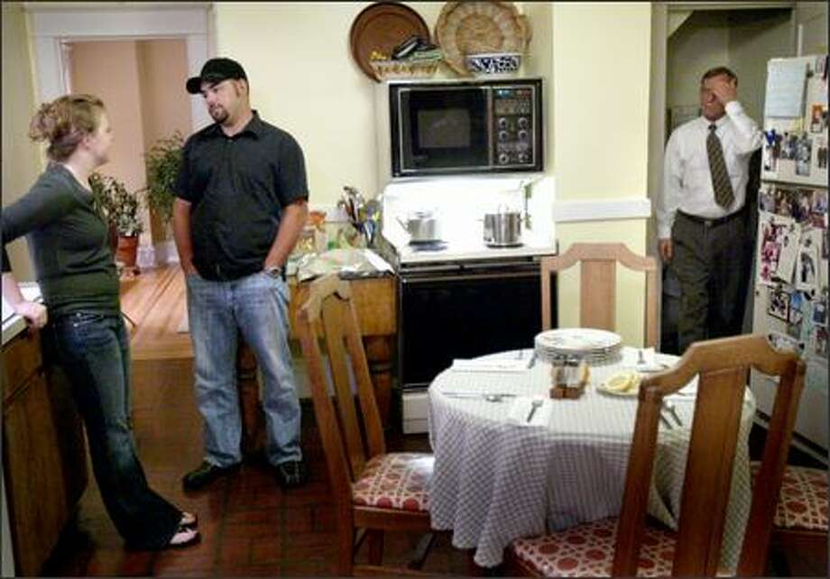 Kate Gwinn and her husband, Jason, have a discussion Wednesday in the Magnolia home of Kate's parents as her dad, Paul David, walks into the room. The couple moved back into Kate's parents' home so they can save enough money to buy a home. Photo: Joshua Trujillo/Seattle Post-Intelligencer