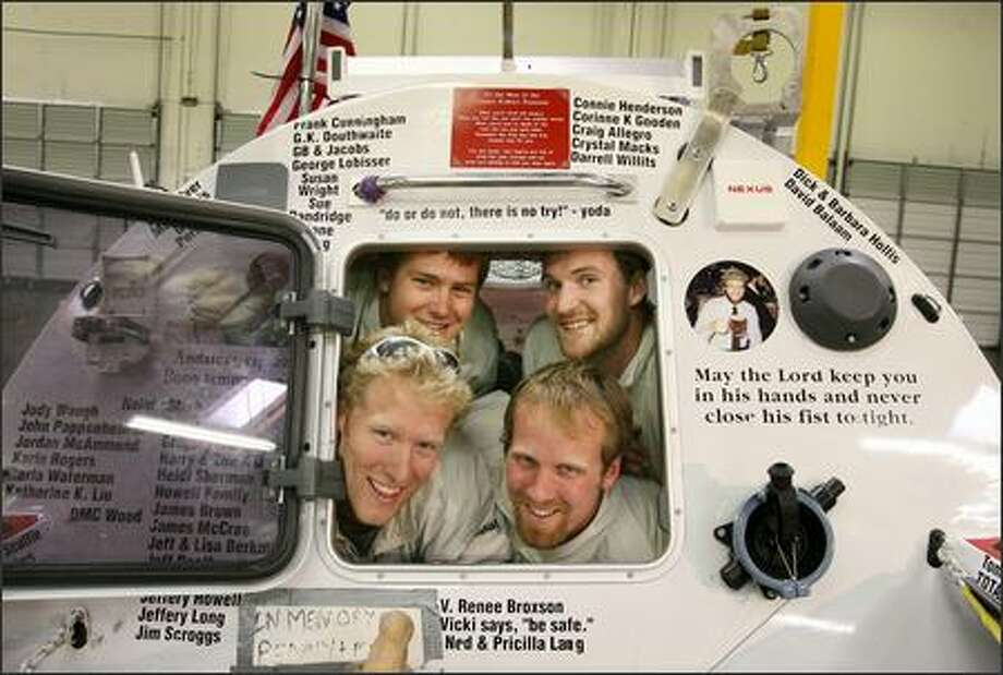 Clockwise from bottom left, rowers Greg Spooner, Dylan LeValley, Jordan Hanssen and Brad Vickers posed Thursday in the cabin of the boat they used to cross the Atlantic Ocean. The foursome crammed into the tiny cabin during storms at sea. Photo: Dan DeLong/Seattle Post-Intelligencer