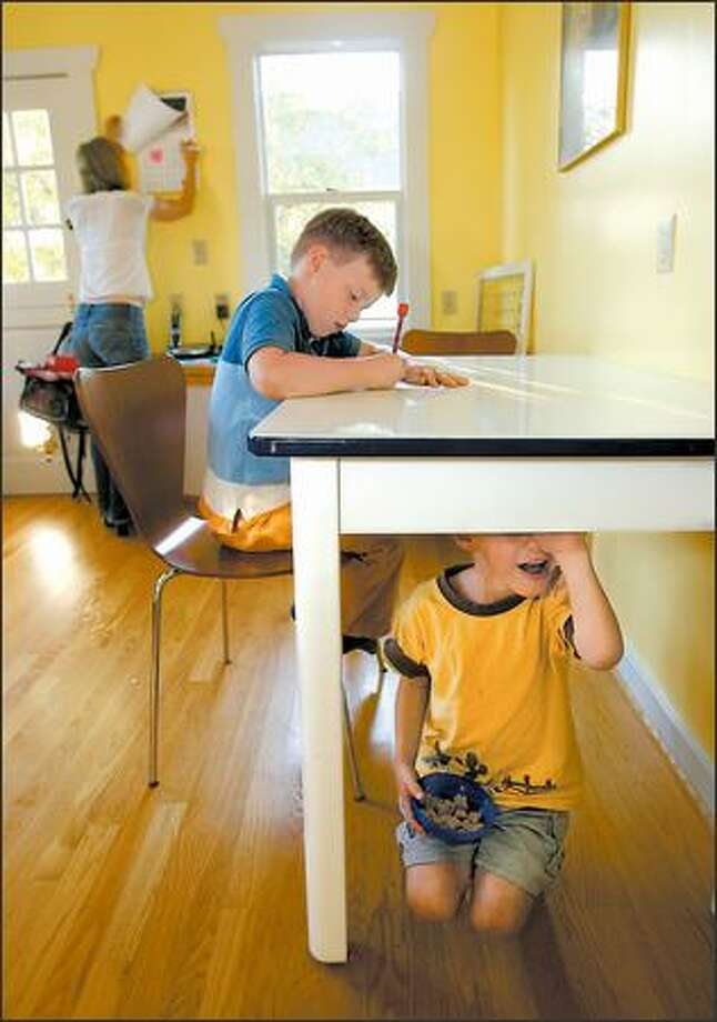 Julian Forester, 7, a second-grader at Loyal Heights Elementary, had a heavy homework load until his mom, Anne, background, got it cut. Brother Brendon, 5, plays under the table. Photo: Scott Eklund/Seattle Post-Intelligencer