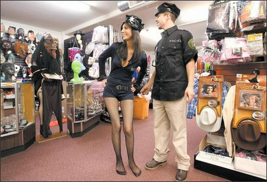 Heather Morgan and Tony Diepenbroch, who are shopping early for Halloween, try on police uniform costumes at Champion Party Supply in Seattle. Photo: Mike Urban/Seattle Post-Intelligencer