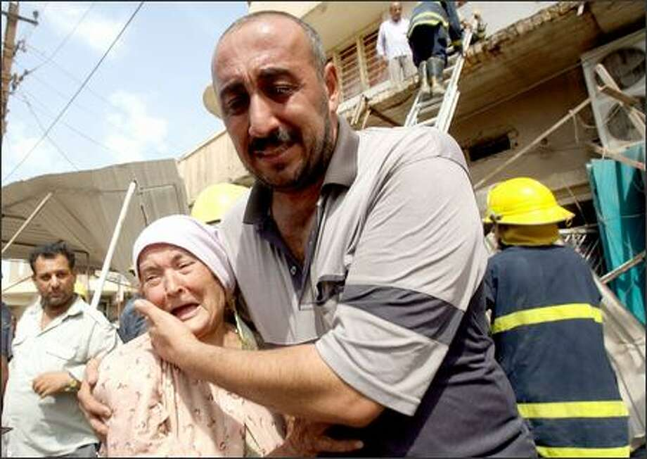 A man comforts an elderly woman after a roadside bomb ripped through an apartment building, killing four and wounding 14 in Baghdad's downtown Al-Nasir Square on Monday. Photo: / Associated Press