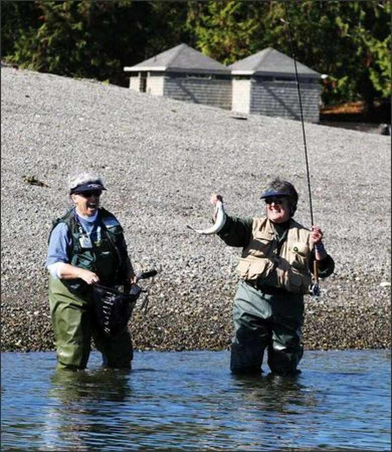 Mary Bohnemeyer of Kenmore shows off a cutthroat trout before releasing it back into South Puget Sound off Harstene Island during a recent Northwest Women Flyfishers outing. Photo: Meryl Schenker/Seattle Post-Intelligencer