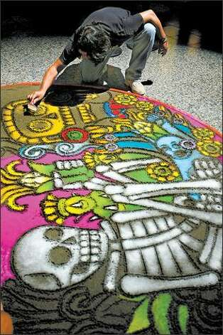 "Mexican-born Seattle artist Isaac Hernandez Ruiz works on his sand painting depicting the circle of life. The Burke Museum commissioned the artist to create the painting and an altar to complement its ""Celebration of Souls"" photo exhibit. Photo: Scott Eklund/Seattle Post-Intelligencer"