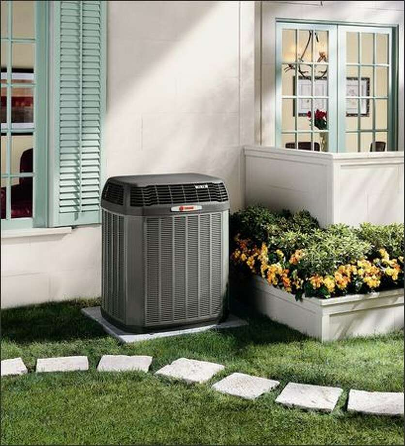 This two-stage outdoor heat pump has a large condenser coil area for high efficiency. Heat pumps are basically central air conditioners that run in reverse during the winter to bring warm air into the house. Photo: TRANE
