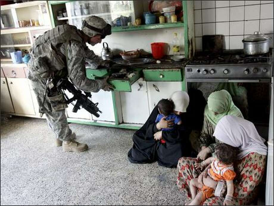 A U.S. soldier searches kitchen drawers in a home in eastern Baghdad Tuesday as women comfort children on the floor. U.S. forces have been staging house-to-house searches to curb violence. Photo: / Associated Press