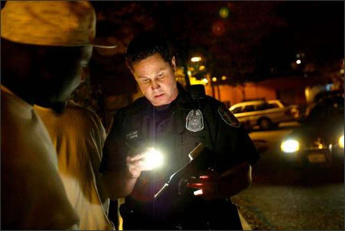 Gang Unit Detective S.D. Cobane checks a youth's identification as he patrols the city streets Saturday looking for gang-related activity.