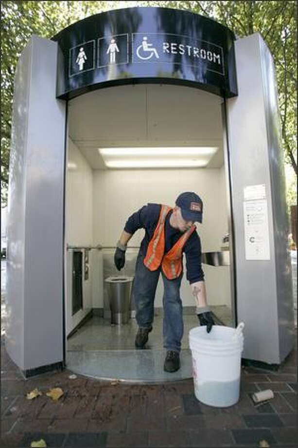 Honey Bucket route driver Joe Powers cleans the automated public toilet in Occidental Square downtown on Wednesday. The city decided in 2004 to spend nearly $700,000 a year to maintain five high-tech toilets. Photo: Mike Kane/P-I