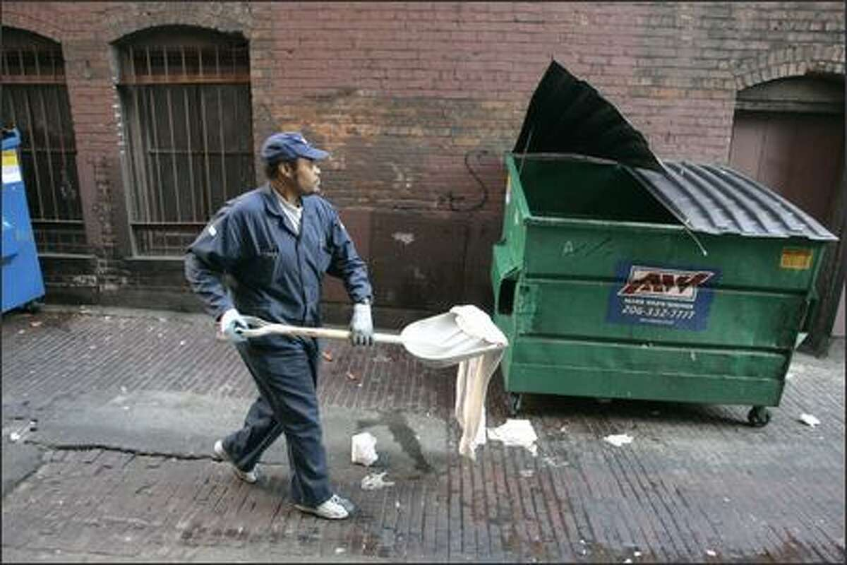 The Metropolitan Improvement District's Reggie Smith shovels trash and feces while cleaning a downtown Seattle alley Wednesday. Despite the public toilets, city streets still contain human waste.