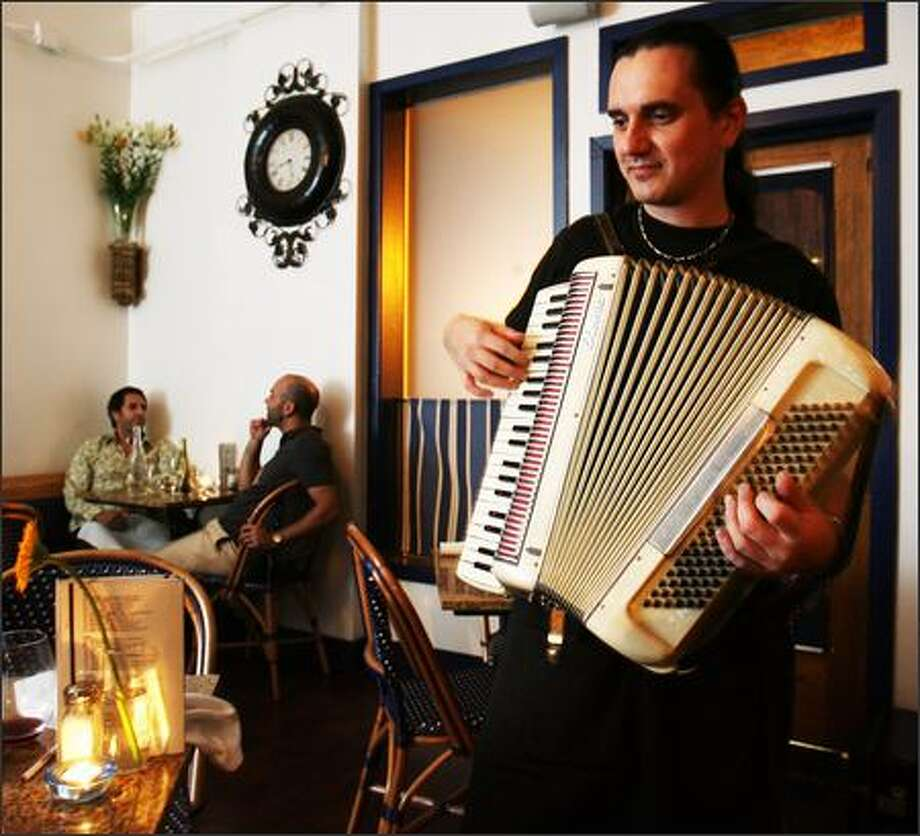 Restaurant owner Jean-Michel Omnès can be found waiting tables, chatting with diners and entertaining them with his accodion playing. Photo: Mike Urban/Seattle Post-Intelligencer