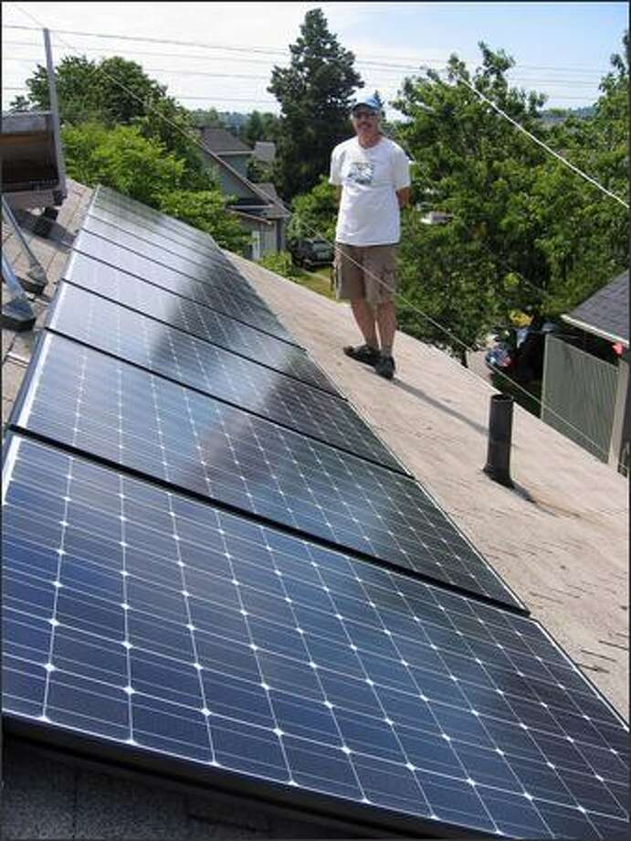 Seattle resident Jack Herndon shows off the photovoltaic roof panels he uses to turn the sun's energy into electricity. Photo: JEREMY SMITHSON PHOTO