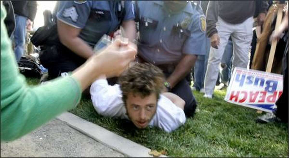 Seattle police officers scuffle with an unidentified man before arresting him at Cal Anderson Park during a protest Thursday against President Bush.