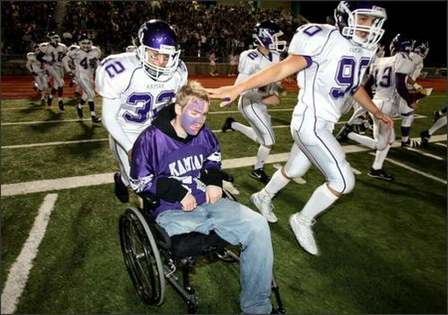 Joe Pyles gets a push from good friend Alex Ashby and a pat from another teammate while taking the field with the Kamiak football team on Friday night. Photo: Mike Urban/Seattle Post-Intelligencer