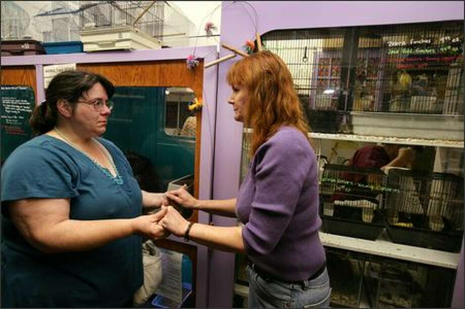 Trish Hurley, left, consoles Missy Young, the owner of Animal Talk, a pet store and animal shelter that was vandalized and robbed early Saturday. Photo: Meryl Schenker/Seattle Post-Intelligencer
