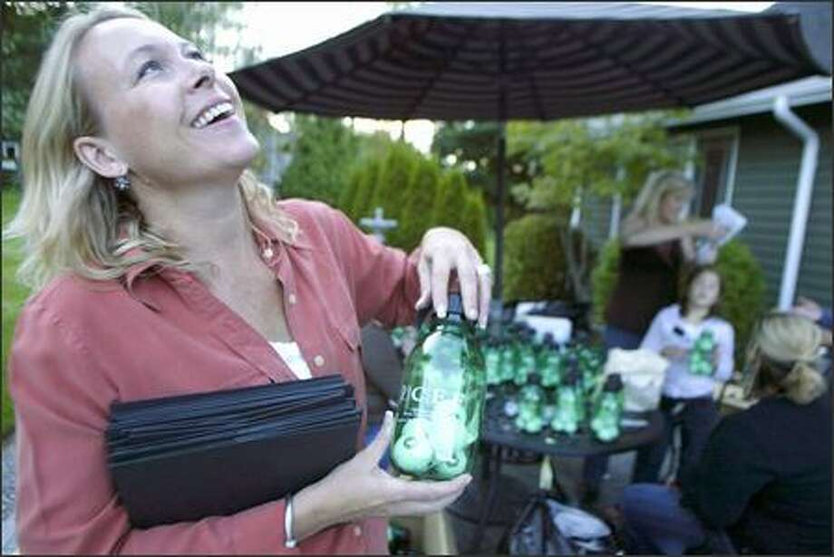 Dellann Elliott, whose husband died from brain cancer five years ago, laughs as she holds a bottle of golf balls that will be given to golfers at a fundraising tournament today at Bear Creek Country Club. Photo: Jim Bryant/Seattle Post-Intelligencer