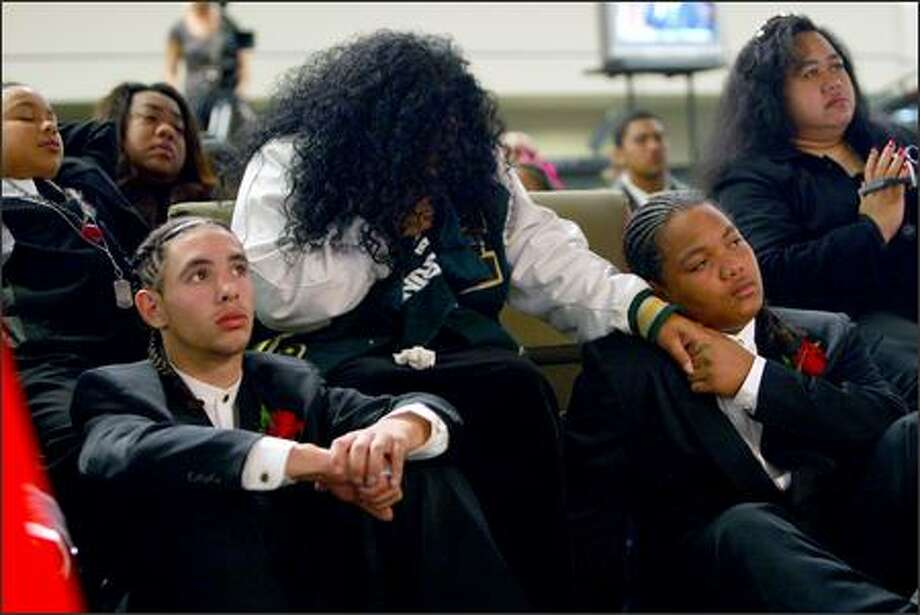 From left, Timothy Miller, one of Michael's brothers, Lena Jantoc, his mother, and Jordan Jantoc, another brother, listen to presentations during the funeral for Michael Miller at the Christian Faith Church in Seatac. Photo: Karen Ducey/Seattle Post-Intelligencer