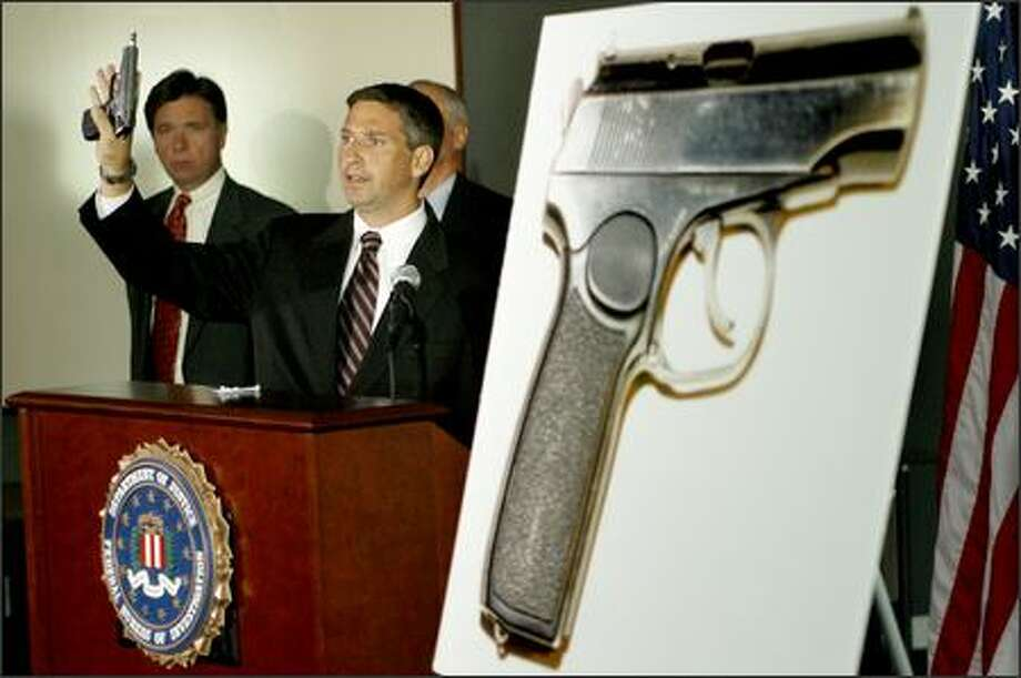 At a news conference at the U.S. District Courthouse, Robert Geeslin of the FBI shows the type of gun used to kill federal prosecutor Tom Wales five years ago in his home. Photo: Dan DeLong/Seattle Post-Intelligencer