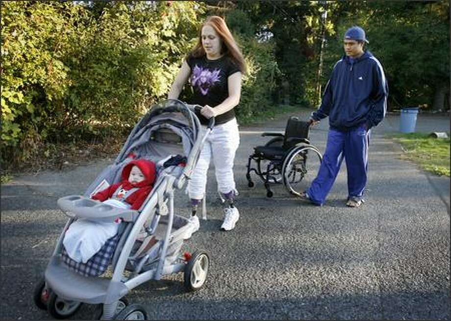 Fitted with lighter, more streamlined prosthetics, Rose Bard, 31, is able to push her baby son, Aries, as her fiancé, Alex Laigo, follows Wednesday near their Edmonds home. Photo: Dan DeLong/Seattle Post-Intelligencer