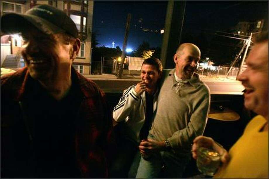 "Gay Fathers Association of Seattle members, from left, Jim Wilkinson, Doug Leighton, Jim Jamerson and Michael Wilson, hang out at the bar Thursday after one of their twice-monthly support group meetings. ""Gays feel completely comfortable going anywhere"" now, not just gay bars, says Thumper's co-owner Nathan Benedict. Photo: Mike Kane/P-I"