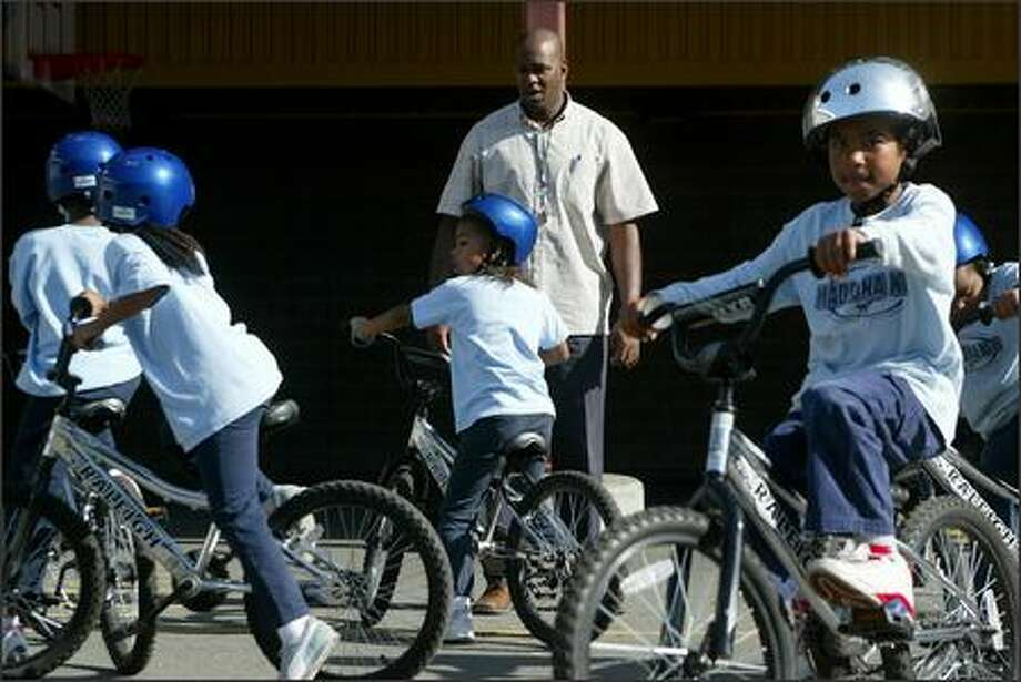 Brad Brown, assistant principal at Madrona K-8 School, stops by one of Madrona's bike classes Tuesday, where first-, second- and third-graders are being taught how to safely ride bikes. Photo: Paul Joseph Brown/Seattle Post-Intelligencer