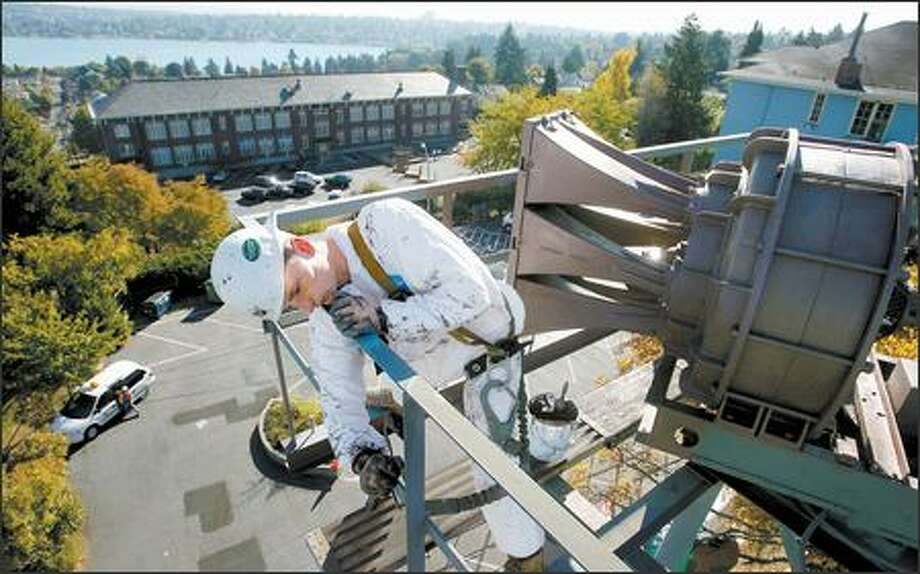 Kevin Waterbury, who works for Purcell Painting & Coatings, paints an intermediate coat on the railing around the air-raid siren at the Phinney Neighborhood Center. Photo: Scott Eklund/Seattle Post-Intelligencer