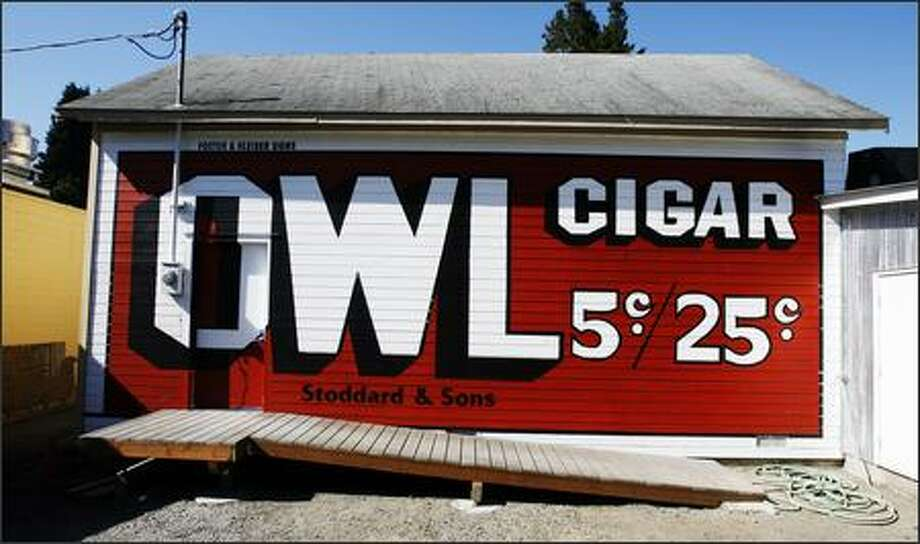 As in the old days, the back side of Issaquah's Front Street Shell Station now howls with an Owl cigar sign, a reproduction of the Foster & Kleiser original. Photo: Gilbert W. Arias/Seattle Post-Intelligencer