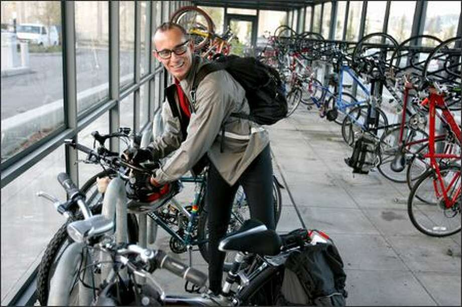 Joe Parsons, who cycles to work at Amgen from his home on Capitol Hill, puts his bike away in the garage. A coalition of business and government organizations is releasing the first annual list of the Puget Sound's Best Workplaces for Commuters. The list spotlights 249 employers and two districts offering superior commuter benefits to 449,600 employees in the Puget Sound area. Photo: Scott Eklund/Seattle Post-Intelligencer