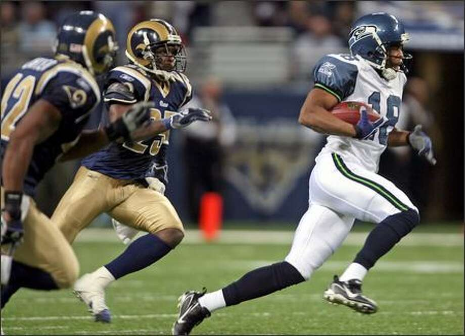 D.J. Hackett, subbing for ailing Bobby Engram, outruns Rams defenders Jerome Carter and Corey Chavous for a clutch 37-yard gain on third-and-12 in Sunday's victory. Photo: Mike Urban/Seattle Post-Intelligencer