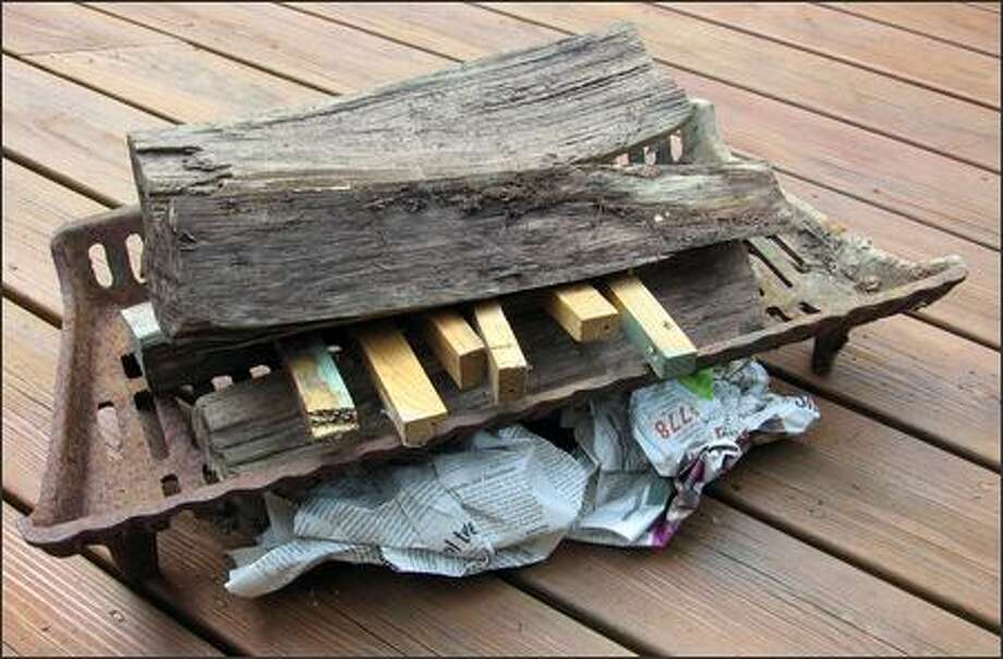 In the English method, kindling is placed on top of the first layers of logs, with a few pieces reaching down into the newspapers. Photo: JIM DULLEY