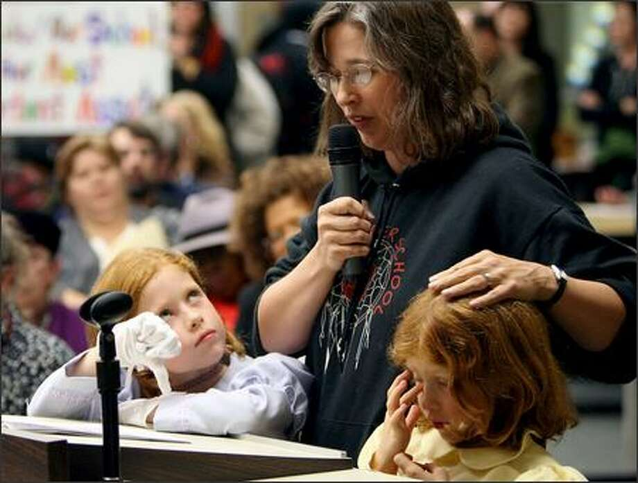Twins Claire, left, and Emma Strevey, 8, support their mom, Beth Bakeman, Wednesday as she speaks before the School Board in opposition to moving the Pathfinder program. Responses by some parents to the superintendent's closure plans were heated. Photo: Mike Urban/Seattle Post-Intelligencer