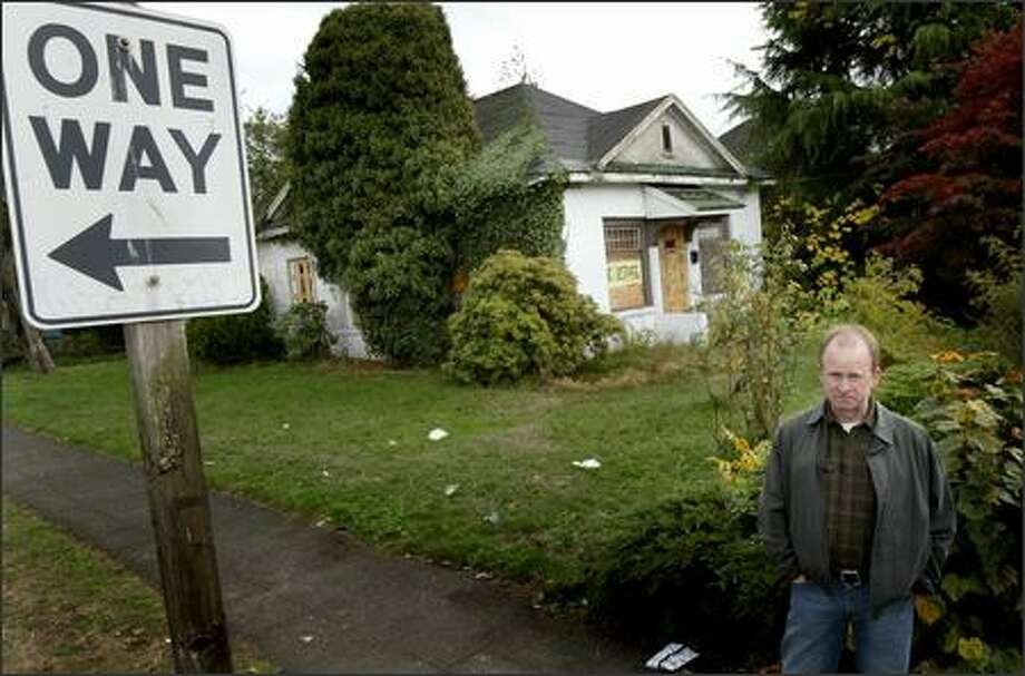 Jim O'Halloran, president of the Roosevelt Neighborhood Association, shows one of Hugh Sisley's houses (this one unoccupied) in the Roosevelt neighborhood Tuesday. Roosevelt neighbors are using momentum from a recent fire at three of the homes to share their concerns with city officials. Photo: Joshua Trujillo/Seattle Post-Intelligencer