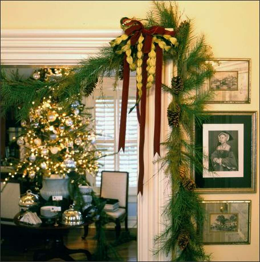 Deck your doorways with twists of feathery pine boughs cinched up with ribbons. Photo: / Scripps Howard News Service
