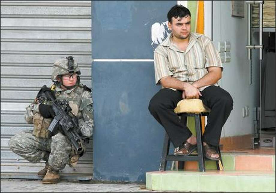 A soldier with the 172nd Stryker Brigade squats by a shopkeeper in Baghdad's cordoned-off Karradah district, where door-to-door searches continued Thursday for a missing officer of Iraqi descent. Photo: / Associated Press
